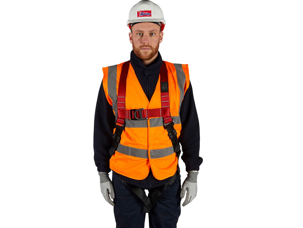A man wearing a high-visability jacket, hard hat, and safety harness