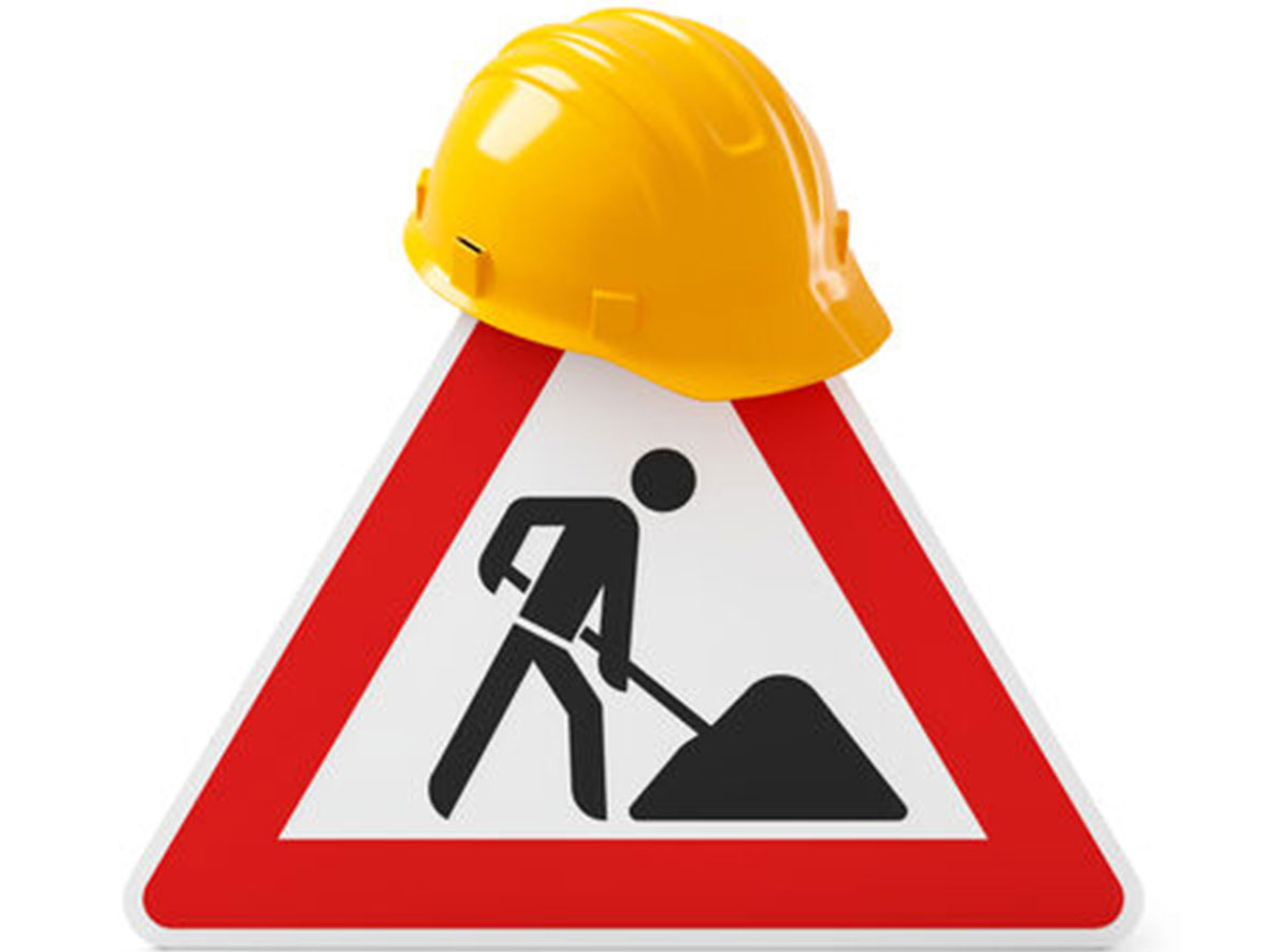 A construction work road sign with hardhat on top of it
