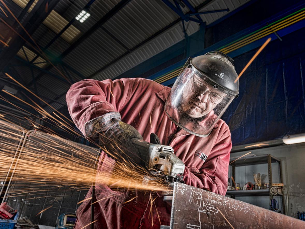 A construction worker using an abrasive wheel power tool