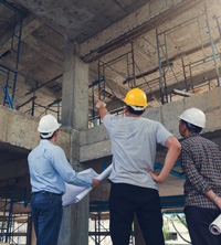 Three construction planners inside an unfinished building that they are working on